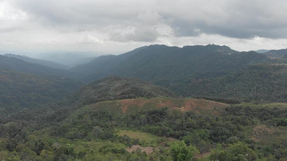 Thumbnail for aerial view of tea plantation on hill and tea pickers village on ridge in dramatic green valley