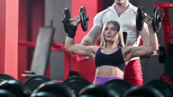 Thumbnail for Woman with Her Personal Trainer in the Gym Exercising with Barbells