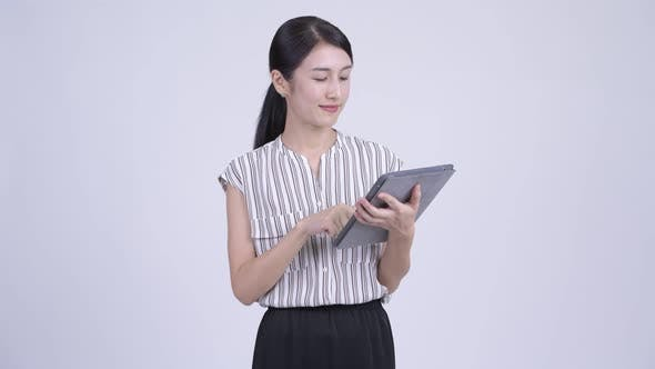 Cover Image for Happy Beautiful Asian Businesswoman Thinking While Using Digital Tablet