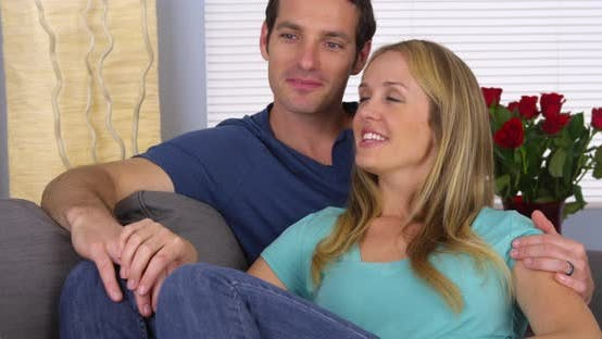Thumbnail for Happy couple sitting together on couch