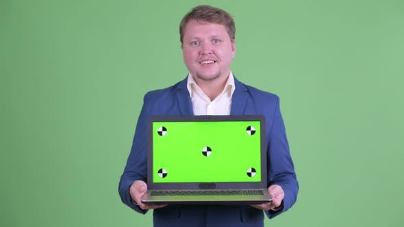 Thumbnail for Happy Overweight Bearded Businessman Thinking and Talking While Showing Laptop