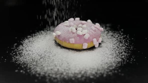 Thumbnail for Tasty Fresh Donut Lay on Black Surface and Gets Sprinkle with Icing Sugar Powder