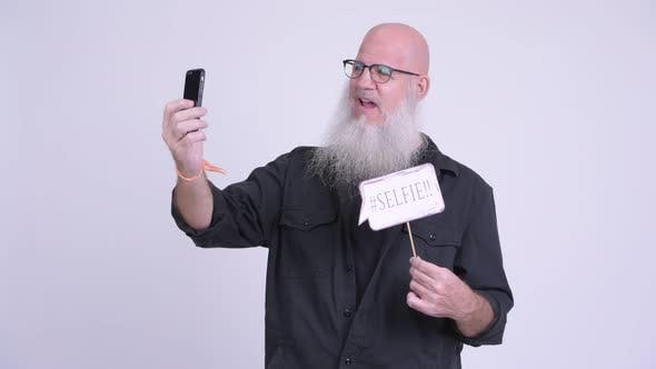 Thumbnail for Happy Mature Bald Bearded Man Taking Selfie with Paper Sign
