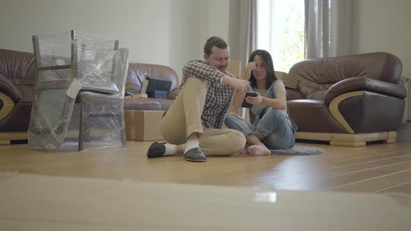 Thumbnail for Happy Caucasian Family Sitting on the Floor in Living Room with New Furniture and Using Smart Phone