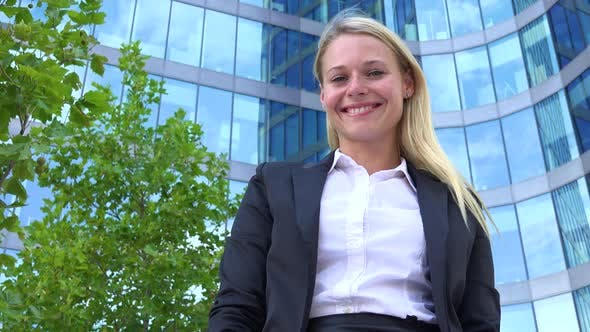 Thumbnail for A Young Beautiful Businesswoman Smiles at the Camera, Turns Around and Walks Into an Office Building