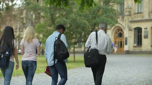 Thumbnail for Multiracial students walking with their dean to academy, chatting about thesis