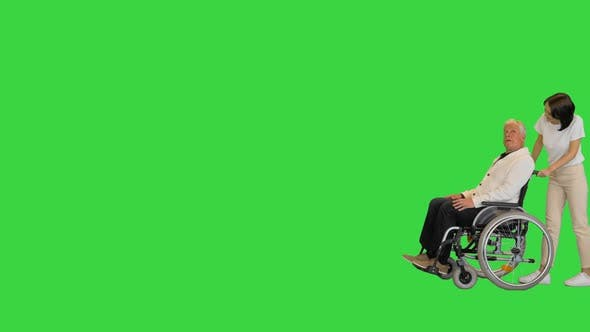 Disabled Senior Man and Assistant Walking By on a Green Screen Chroma Key