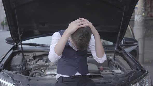 Thumbnail for The Young Stressed Well-dressed Boy Standing in Front of the Broken Car with an Open Hood