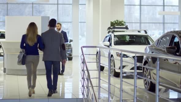 Thumbnail for Cheerful Salesman Helping Couple at Dealership