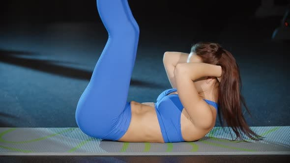 Cover Image for Woman Athlete Sit Ups Exercises Lifting Legs and Torso Abs Crunches Workout on Floor Mat