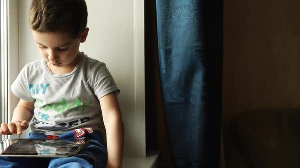 Thumbnail for Child sits on a windowsill and uses a digital tablet pc