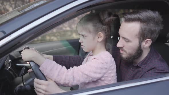 Thumbnail for Little Girl Sitting on Father's Lap in the Car