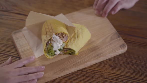 Tasty Shawarma with Sauce Lying on the Wooden Board