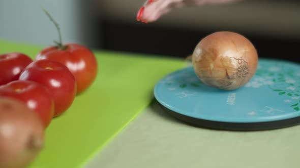 Woman Weighs Vegetables on Scales in the Kitchen Healthy Food Onion