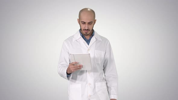 Thumbnail for Mature Male Doctor Holding Digital Tablet Using It and Walking on Gradient Background.