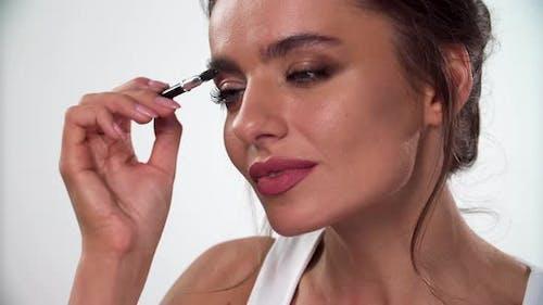 Eyebrows Makeup. Woman Combing Eyebrow With Brush Closeup