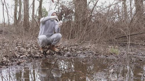 An ecologist takes a water test in a river.