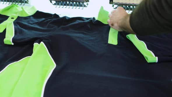 Thumbnail for Man in a Textile Factory Checking the Sewing on T-shirt