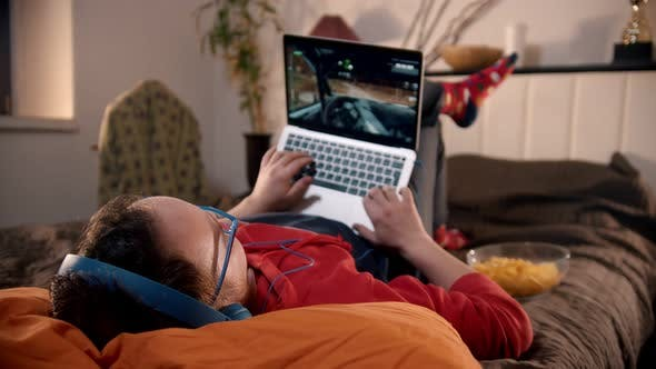 Young Man Lying on the Bed Playing Video Game on the Laptop