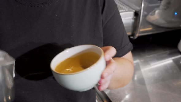 Thumbnail for Cropped Shot of a Barista Adding Hot Milk Into Coffee in a Cup