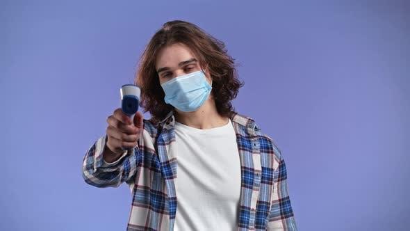 Man in Schutzmaske leitet Elektronisch berührungsloses Thermometer in Kameraobjektiv und misst
