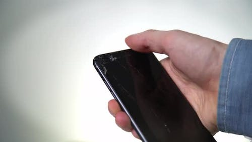 Concept of Smart Phone with Broken Screen. Top View of Man Hands Holding a Phone with Cracked