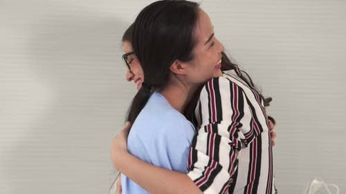 Happy Friends Take Off Face Mask and Hug Each Other Closely Together