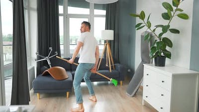 Man Cleaning the House and Having Fun Dancing with a Broom