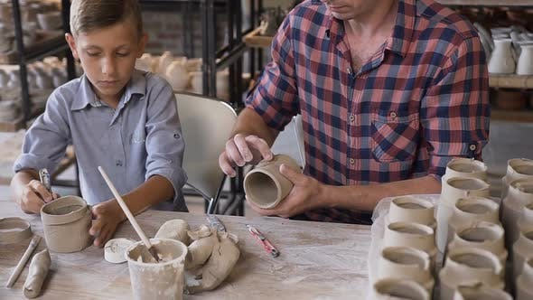 Thumbnail for Little Cute Boy With His Father Making Ceramic Pots in the Pottery