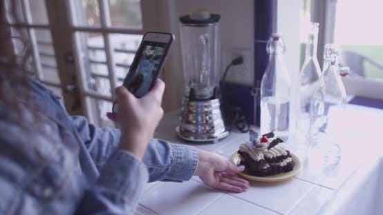 Thumbnail for A beautiful young brunette taking pictures of dessert
