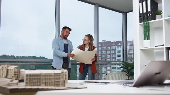 Thumbnail for Mann und Frau mit Dreadlocks stehen im Designbüro und diskutieren Blueprint