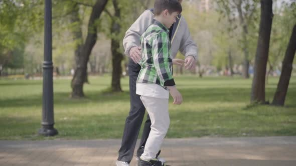 Thumbnail for Portrait Grandfather Teaching His Grandson To Ride Roller Skates in the Park