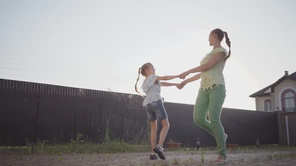 Thumbnail for Happy Little Cute Girl and Her Mother Spinning Around Holding Hands in the Backyard
