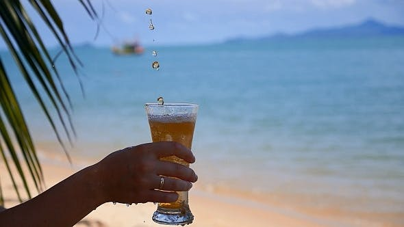 Thumbnail for Female Hand with a Glass of Ice Tea on the Beach
