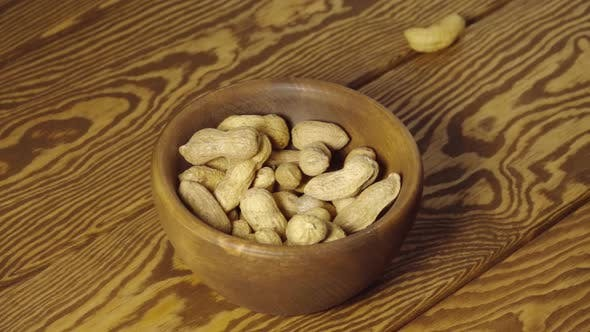 Peanuts fall into wooden cup