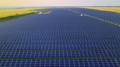 Aerial Drone View Into Large Solar Panels at a Solar Farm at Bright Sunset