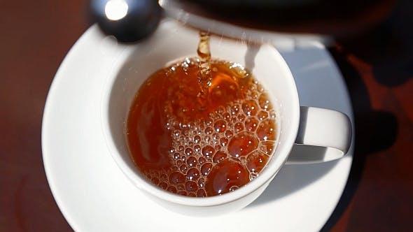Gießen Tee in Tasse