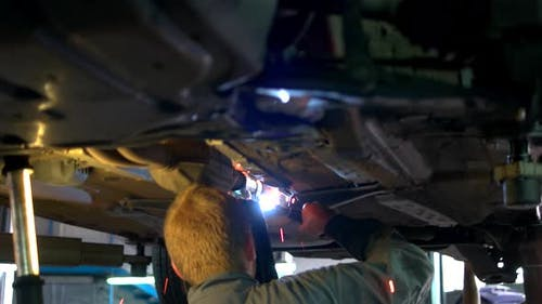Closeup Welding Work on a Lifted Car
