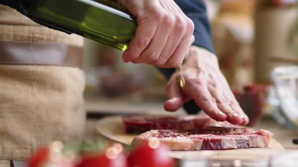 Thumbnail for Close Up View of Male Chef Pouring Olive Oil over Raw Meat Steak