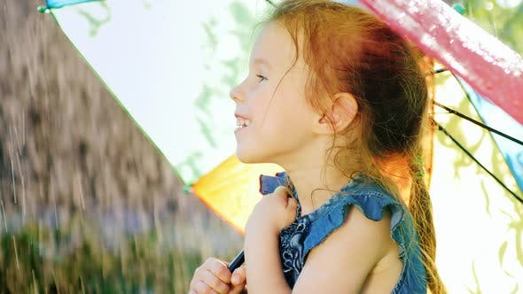 Portrait in Profile of a Carefree Girl Who Enjoys the Rain.