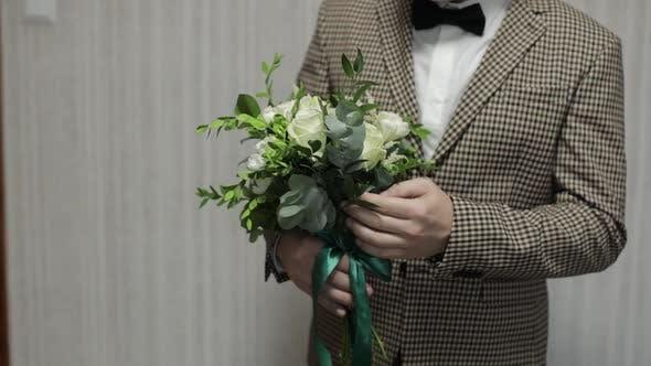 Thumbnail for Bräutigam mit Hochzeitsstrauß in seinen Händen zu Hause. Weißes Hemd, Jacke. Nahaufnahme. Zeitlupe