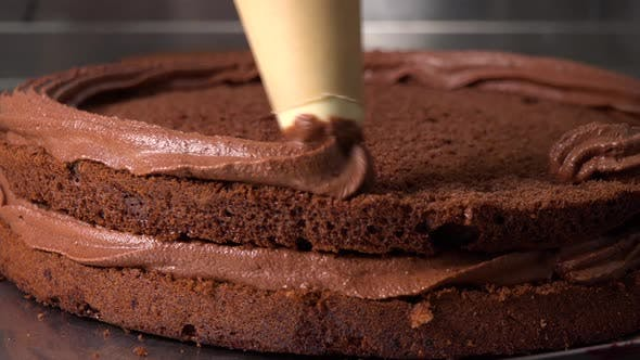 Thumbnail for Chocolate Frosting Is Applied Onto the Layers of a Dark Cake Base - Closeup