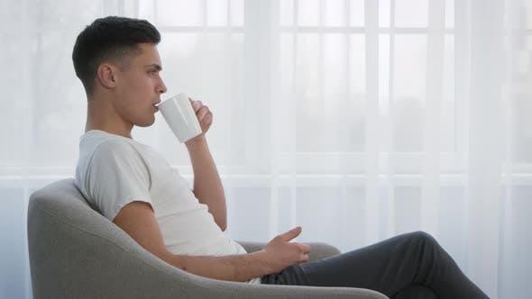 Seitenansicht Porträt eines jungen Mannes, der sich im gemütlichen Sessel ausruht und Zeitlupe genießt