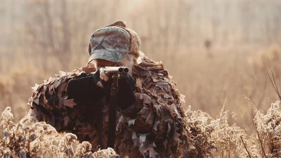 Thumbnail for Portrait of Hunter in Hunting Equipment Aims with Shot Gun, Lies in Wait in Field in Sunset Light