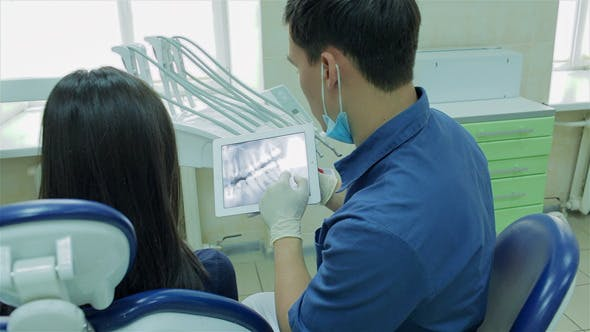 Cover Image for Dentist Shows A Patient X-ray On The Tablet
