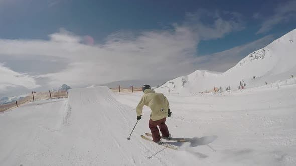 Thumbnail for A young man freestyle skier skiing and going off jumps in a terrain park on a snow covered mountain.