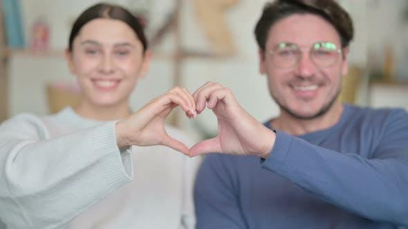 Portrait of Happy Hispanic Couple Holding Hands in Heart Shape