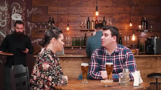 Thumbnail for Couple Being Served with a Pizza in Vintage Pub or Restaurant