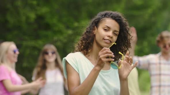 Thumbnail for Hübsche Frau in Sonnenbrille Tanzen mit Freunden im Sommer Camp, Jugendlichkeit