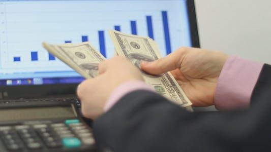 Thumbnail for Businessman Counts Dollars Amid Laptop